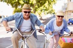 Lyckliga mogna par som går för en cykel, rider i staden Arkivfoton