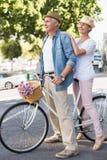 Lyckliga mogna par som går för en cykel, rider i staden Royaltyfri Foto