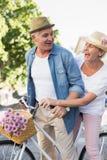 Lyckliga mogna par som går för en cykel, rider i staden Royaltyfria Foton