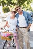 Lyckliga mogna par som går för en cykel, rider i staden Royaltyfri Bild