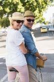 Lyckliga mogna par som går för en cykel, rider i staden Royaltyfria Bilder