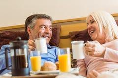 Lyckliga mogna par som har frukosten i säng Royaltyfri Fotografi
