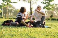 Lyckliga mogna par som sitter i, parkerar på matt kondition och att vila dricka yoghurt efter sportövningar royaltyfria bilder
