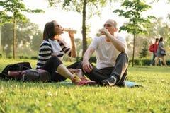 Lyckliga mogna par som sitter i, parkerar på matt kondition och att vila dricka yoghurt efter sportövningar royaltyfri fotografi
