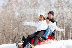 Lyckliga mogna par som sledding Royaltyfria Bilder