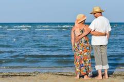 Lyckliga mogna romantiska par som vilar på kusten och att omfamna Royaltyfri Bild
