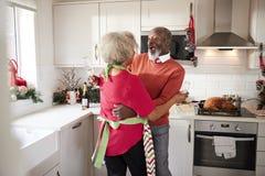 Lyckliga mogna svarta par som rymmer champagneexponeringsglas, skrattar och omfamnar i köket, medan förbereda mål på julmorni arkivbilder