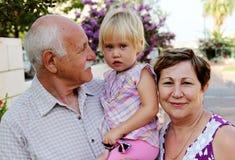 Lyckliga morföräldrar med barnbarnet arkivbild