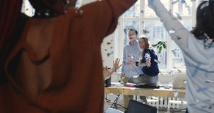 Lyckliga multietniska kollegor firar framgång samman med konfettier, ung kvinnlig stol för kontor för företagsframstickanderidnin lager videofilmer