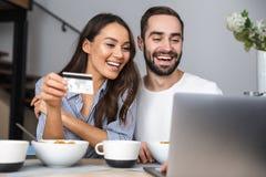 Lyckliga multietniska par som har frukosten arkivfoton