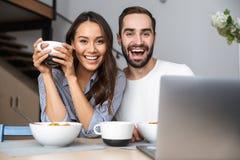 Lyckliga multietniska par som har frukosten royaltyfria foton