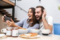 Lyckliga multietniska par som har frukosten royaltyfri bild