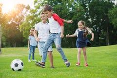 Lyckliga multietniska ungar som spelar fotboll med bollen parkerar in Royaltyfri Foto