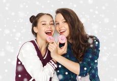 Lyckliga nätta tonårs- flickor som äter donuts Royaltyfri Fotografi