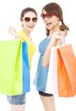 Lyckliga nätta unga systrar som rymmer shoppingpåsar Royaltyfri Foto