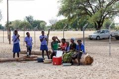Lyckliga namibiska skolbarn som väntar på en kurs Arkivfoto
