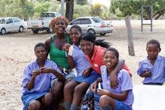 Lyckliga namibiska skolbarn som väntar på en kurs Arkivfoton