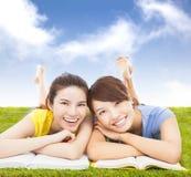 Lyckliga nätta studenter som ligger på grässlätten med böcker Royaltyfria Bilder