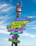 2015 lyckliga nya år i franskt på pastell färgade träriktningstecken Arkivfoto