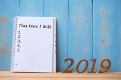 """2019 lyckliga nya år med anteckningsbok"""", i år som jag skallr """"text och tränumret på tabell- och kopieringsutrymme royaltyfri foto"""