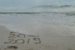 Lyckliga nya år 2017, 2018 och 2019 som är handskrivna på sand royaltyfri foto