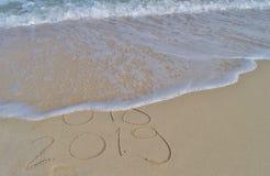 Lyckliga nya år 2018 och 2019 som är handskrivna på sand arkivbild