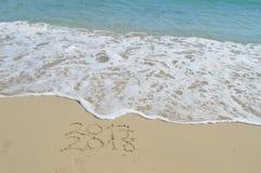 Lyckliga nya år 2017 och 2018 som är handskrivna på sand Royaltyfria Foton