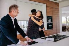 Lyckliga nya egendomsägare med fastighetsmäklare Royaltyfri Bild