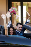 Lyckliga nygift person i cabrio royaltyfri bild