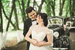 Lyckliga nygift personpar, man och fru som kysser nära den stilfulla retro bilen Arkivbild