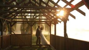 Lyckliga nygift personpar som kysser i strand, utgjuter dörröppningen på aftonen av bröllopdagen nära sjön för bergsemesterorten  stock video