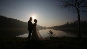 Lyckliga nygift personpar som omfamnar nära stranden som utgjutas på aftonen av bröllopdagen på sjön för bergsemesterort på solne stock video