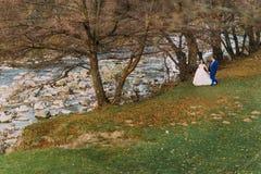 Lyckliga nygift personpar som strosar på den steniga kiselstenflodbanken med träd och ström som bakgrund Royaltyfri Fotografi