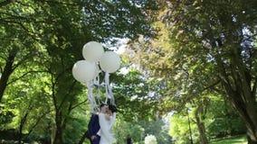 Lyckliga nygifta personer är krama ömt, och kyssa i vår parkera Bruden är hållande vita ballonger stock video