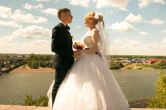Lyckliga nygifta personer, brud och brudgum som poserar på floden med härliga sikter Royaltyfri Fotografi