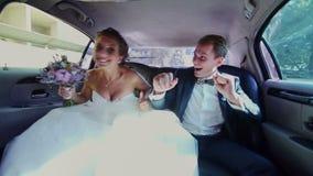 Lyckliga nygifta personer som har gyckel i en Limo stock video