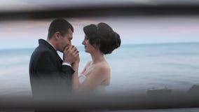 Lyckliga nygifta personer som kramar och kysser, medan stå nära havet på solnedgången arkivfilmer