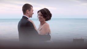 Lyckliga nygifta personer som kramar och kysser, medan stå nära havet på solnedgången stock video