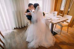 Lyckliga nygifta personer som omfamnar och talar av deras nya gifta liv i restaurang på tabellen Arkivbilder