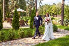 Lyckliga nygifta personer som rymmer händer och går på gångbanan i sommar p royaltyfria bilder