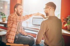 Lyckliga och emotionella män sitter tillsammans och att skrika De har satt deras nävar tillsammans Bilden är positivt Fotografering för Bildbyråer