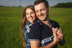 Lyckliga och förälskade tonåringar som omfamnar i ett fält Arkivfoto