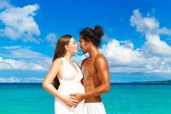 Lyckliga och för barn gravida par som har gyckel på en tropisk strand Arkivbilder