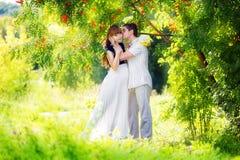 Lyckliga och för barn gravida par som kramar i parkera Sommarvaca Fotografering för Bildbyråer