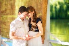 Lyckliga och för barn gravida par som kramar i parkera Sommarvaca Arkivfoto