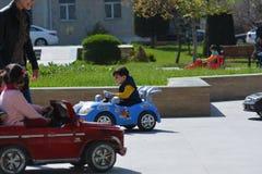 Lyckliga och glade barn rider bilar parkerar in Royaltyfri Fotografi