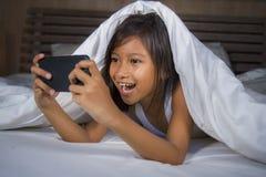 Lyckliga och härliga 7 år gammalt barn som har den roliga spela internetleken med mobiltelefonen som ligger på säng som är gladly royaltyfria foton