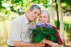 Lyckliga och mycket gamla par som ler i, parkerar på en solig dag fotografering för bildbyråer