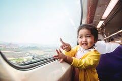 Lyckliga och upphetsade ungar som reser med drevet Två år en gammal flicka arkivbilder