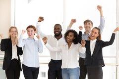 Lyckliga olika anställda som firar seger och framgång på arbete royaltyfria foton